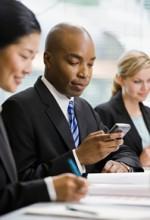 businessman text messaging during meeting